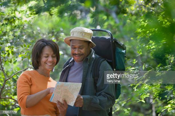 African couple hiking with map in woods
