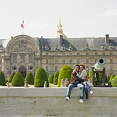 African couple hugging and sitting on stone wall next to cannon