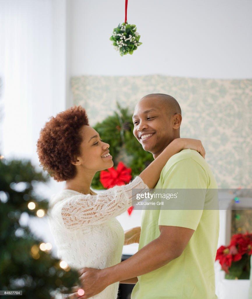 African couple kissing underneath mistletoe