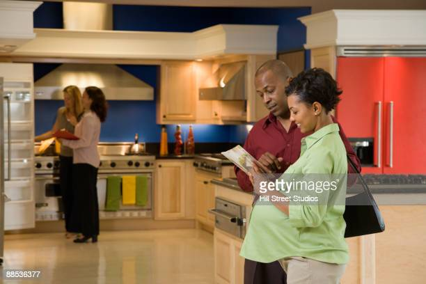 African couple looking at brochure in kitchen showroom