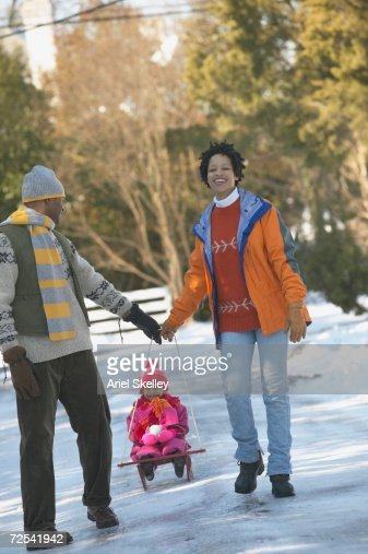 African couple pulling child on sled