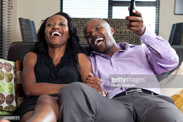 African Couple Relaxing Together At Home Watching TV And Laughing