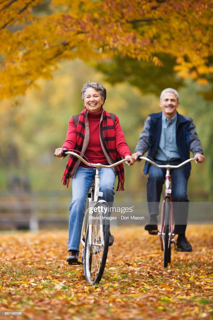 African couple riding bicycles in park in autumn : Stock Photo