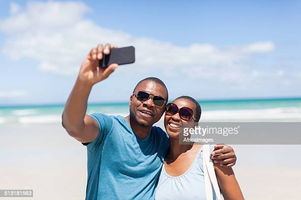 Casal africano tendo um selfie juntos na praia