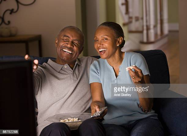 African couple watching television and eating popcorn