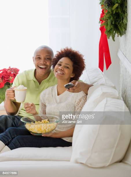 African couple watching television with popcorn and hot chocolate