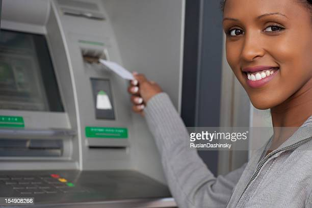 African decent woman withdrawing money from credit card at ATM.