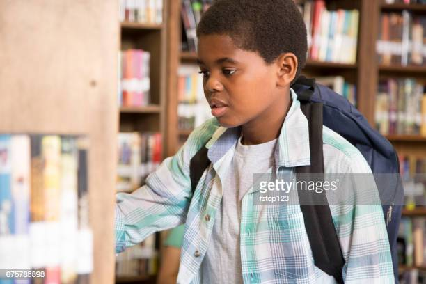 African descent boy in school library choosing book.