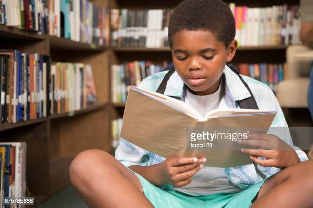 African descent boy in school library reading book.