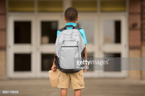African descent, little boy faces school building. Lunch, backpack.