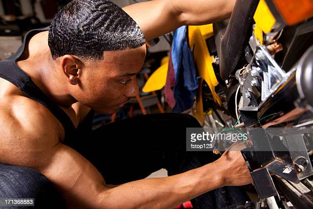 African descent man mechanic working on motorcycle. Repairs.