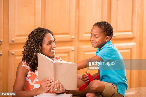 African descent mother and son doing homework together at home.