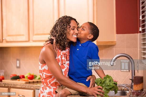 Afrikanischer Herkunft Mutter Vorbereitung Salat.  Son kissing. Küche.