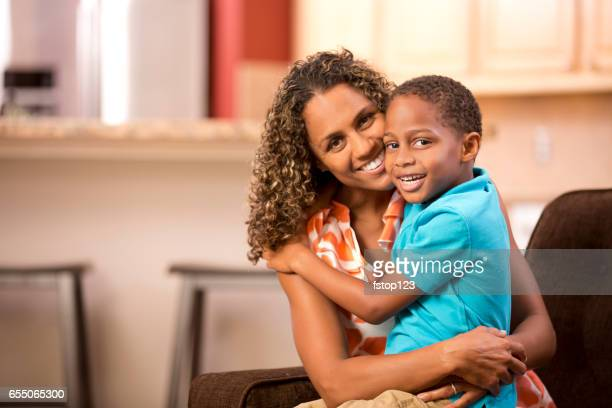 African descent single mother hugs young son at home..