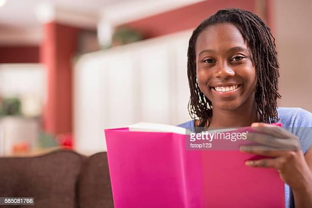 African descent teenage girl studying, reading book at home.
