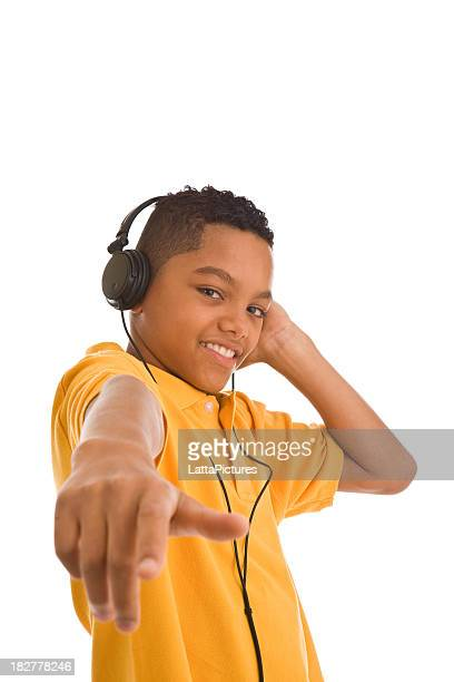African descent teenager wearing headphones and pointing at camera