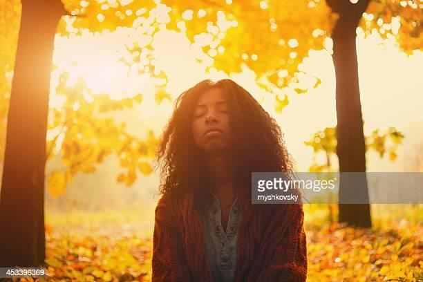 D'origine africaine femme en automne de la lumière du soleil.