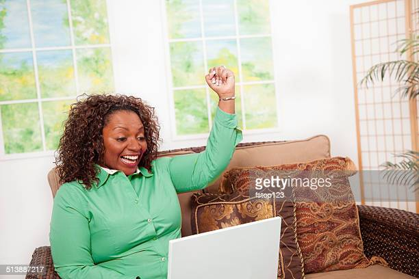African descent woman excitedly views internet program.