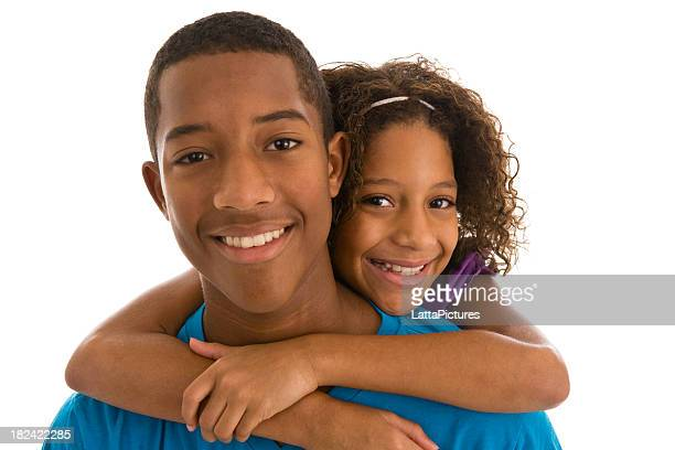African descent young man little sister hugging him from behind