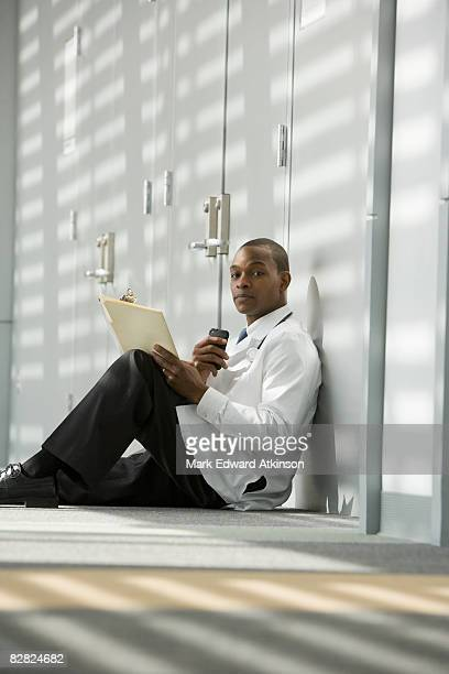 African doctor sitting on floor dictating medical record into recorder