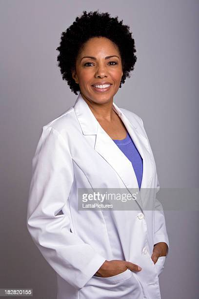 African ethnicity female wearing lab coat hands in pockets