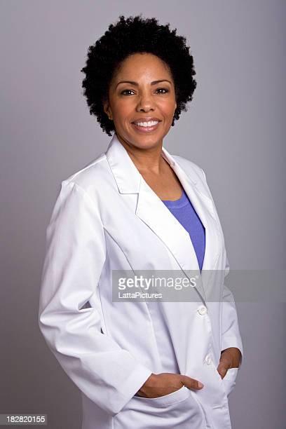 アフリカ系アメリカ人の女性が着ているラボコートポケットに手を入れている
