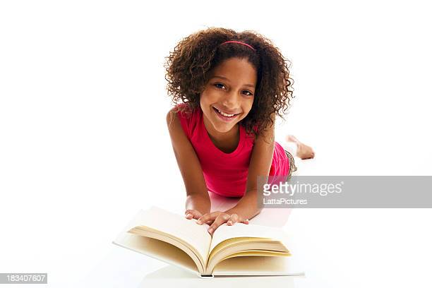 African ethnicity girl lying on front reading book