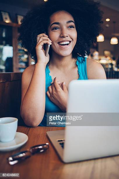 African ethnicity girl with smart phone and laptop