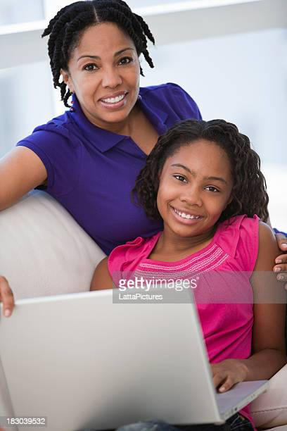 African ethnicity mother and daughter with laptop