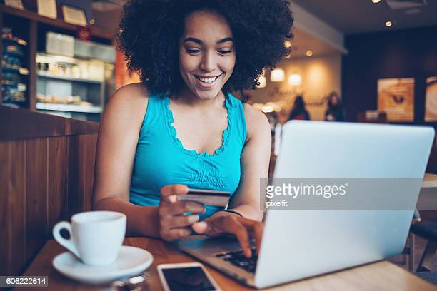 African ethniciy girl shopping on-line in restaurant