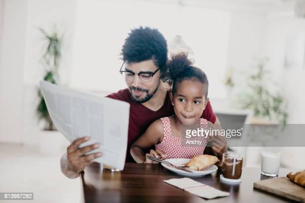 Afrikanische Familie ist Croissants zum Frühstück Essen.
