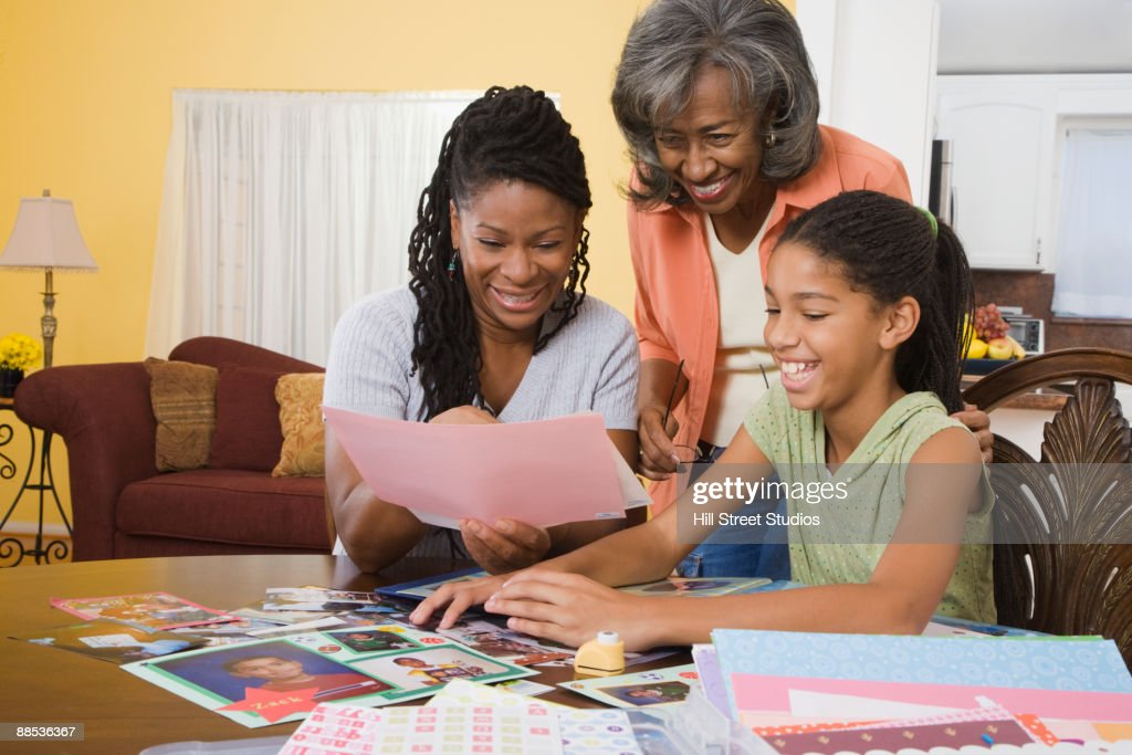 African family making scrapbook together : Stock Photo