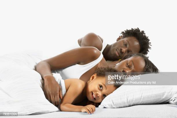 African family sleeping in bed