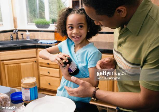 African father and daughter making peanut butter and jelly sandwich