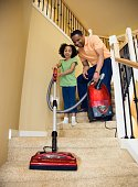 African father and daughter vacuuming stairs