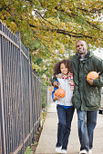African father and daughter walking with pumpkins