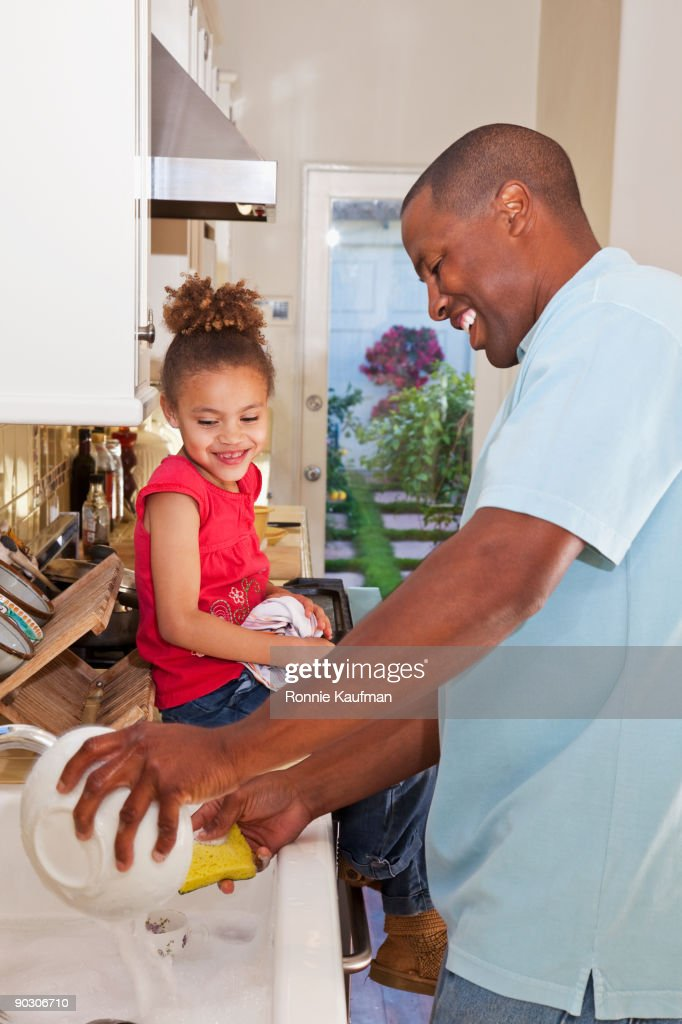 African father and daughter washing dishes : Stock Photo