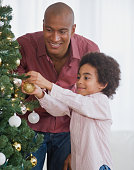African father and son decorating Christmas tree