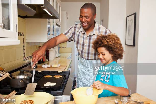 African father and son making pancakes