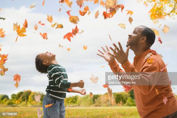 African father and son throwing autumn leaves in air