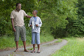 African father and son walking on remote road