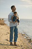 African father holding baby at beach