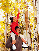 African father holding daughter on shoulders