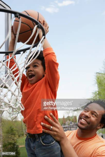 African father lifting son to basketball hoop