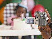 African father videotaping baby in high chair with birthday cake