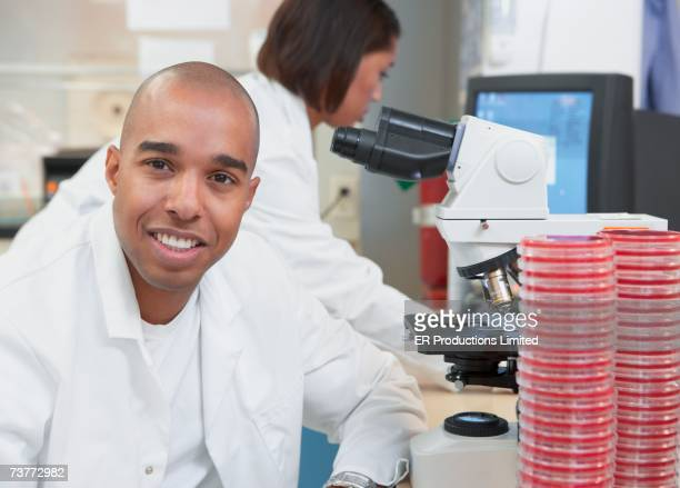 African female and male scientists Petri dishes and microscope