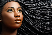 Close up cosmetic beauty portrait of african woman showing long black braided hairstyle.