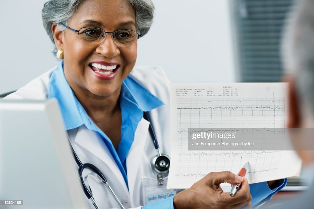 African female doctor explaining electrocardiogram to patient : Stock Photo
