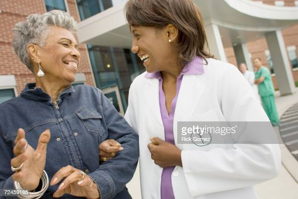 African female doctor laughing with senior African woman outdoors