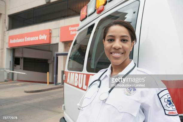 African female EMT next to ambulance